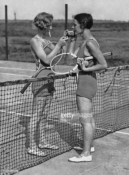 Two women lighting cigarettes on a tennis court in Essex England circa 1930's