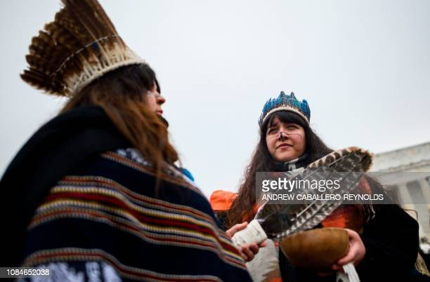 Two women listen to speakers during the Indigenous People's March on the National Mall at the Lincoln Memorial in Washington DC on January 18 2019