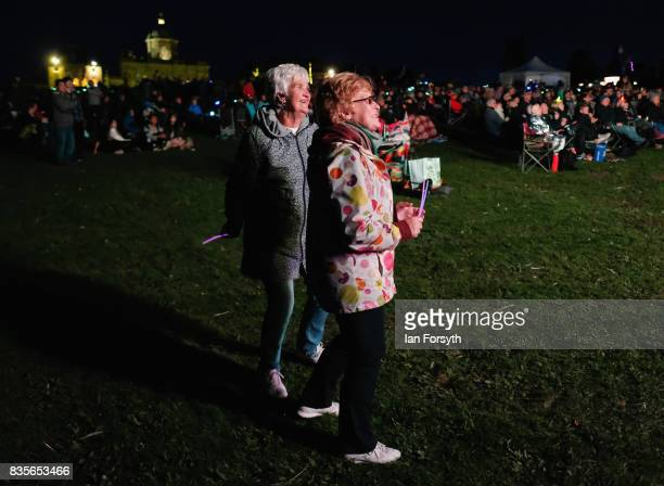 Two women listen to the performance during the annual Castle Howard Proms Spectacular concert held on the grounds of the Castle Howard estate on...