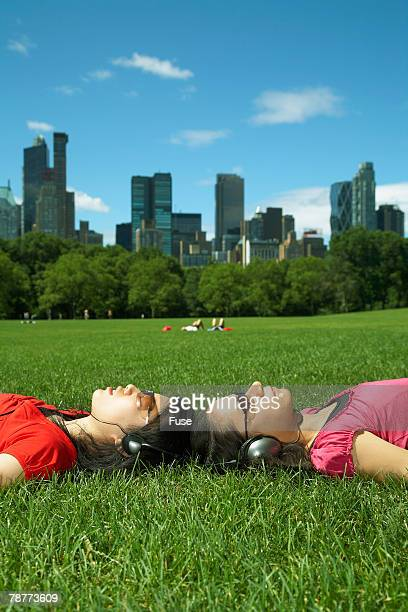 two women listening to music in park - ニューヨーク郡 ストックフォトと画像