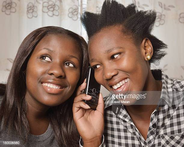 two women listening to one phone call, gugulethu, cape town - gugulethu stock pictures, royalty-free photos & images