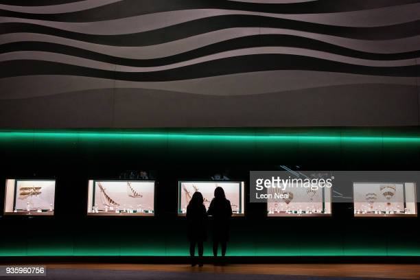 Two women look at a display of Rolex watches at the BaselWorld watch fair on March 21 2018 in Basel Switzerland The annual watch trade fair sees the...