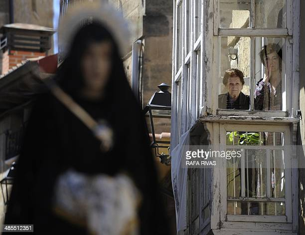 Two women look at a figure representing 'La Dolorosa Virgen' from a balcony during the 'Santa Vera Cruz' brotherhood procession of the Holy Week in...