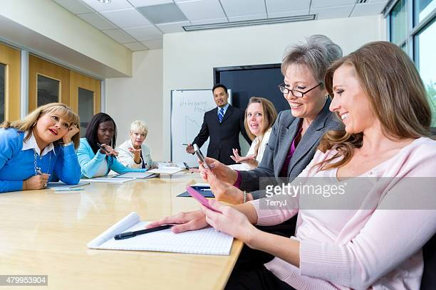 Two Women Look at Cell Phones at a Business Meeting