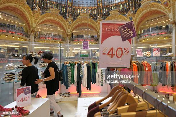 Two women look at clothes at the Galeries Lafayette shopping center on the last day of sales in Paris on August 3 2010 AFP PHOTO / MIGUEL MEDINA