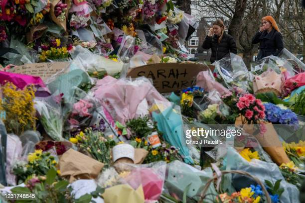 Two women look at floral tributes left at Clapham Common bandstand where people continue to pay their respects to Sarah Everard on March 16, 2021 in...