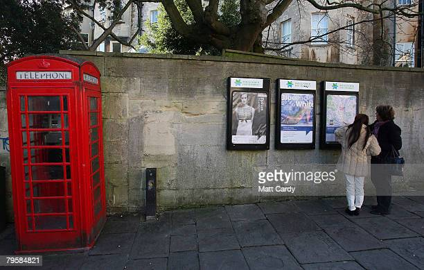 Two women look at posters on a wall beside a traditional red telephone box on a street in Bath on February 6 2008 in Somerset England According to BT...