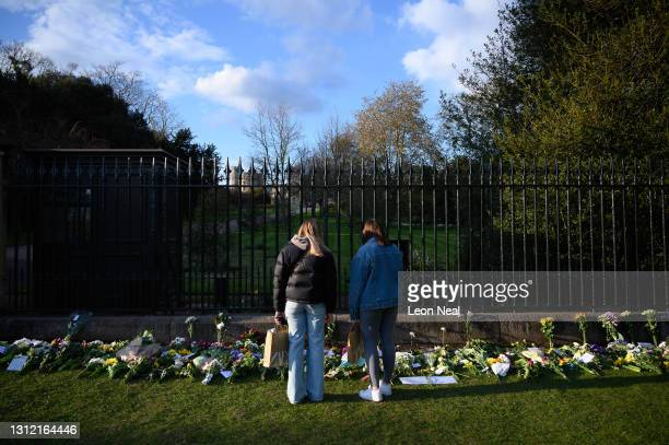 Two women look at some of the flowers left outside the grounds of Windsor Castle, as tributes continue to be made to Prince Philip, the Duke Of...