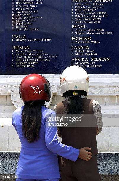 Two women look at the names of the victims of October 12 Bali bombings inscribed on a monument in Kuta Bali 11 October 2004 one day before the...