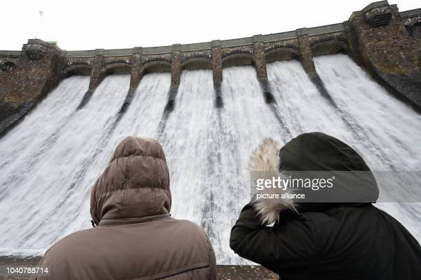 Two women look at the overflowing Diemel dam in Diemelsee Germany 11 February 2016 The reason is a high inflow of water from snow that is melting due...
