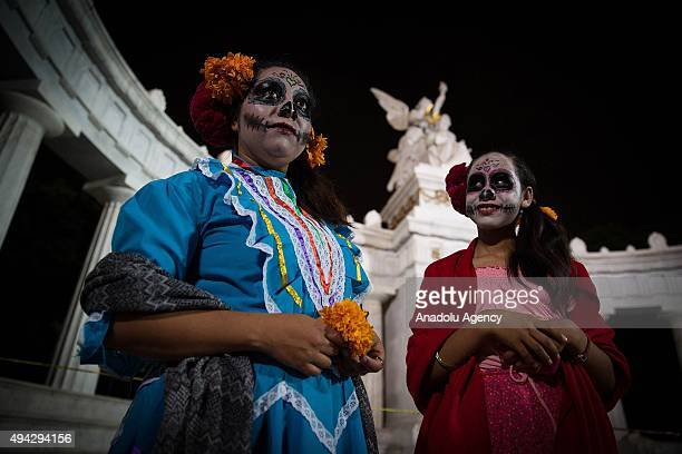 Two women look on during Procession of the Catrinas in Mexico City Mexico on October 25 2015 The Catrina is a figure of a skeleton wearing an elegant...