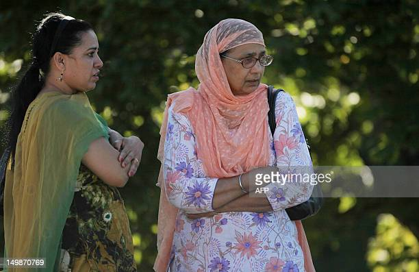 Two women look on near the Sikh Temple of Wisconsin where at least one gunman fired upon people at a service on August 2012 Oak Creek Wisconsin At...