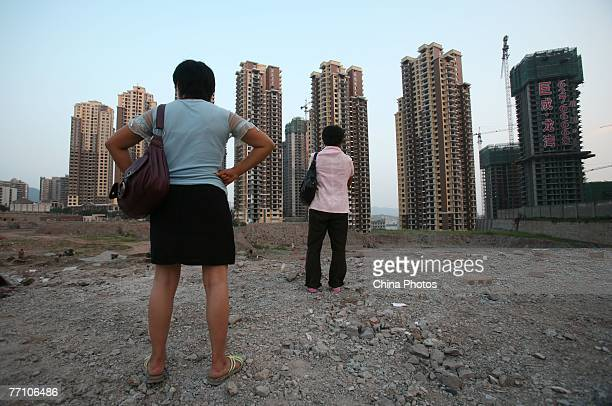 Two women look over buildings under construction near the People's Bank of China office building on September 29 2007 in Chongqing China The People's...
