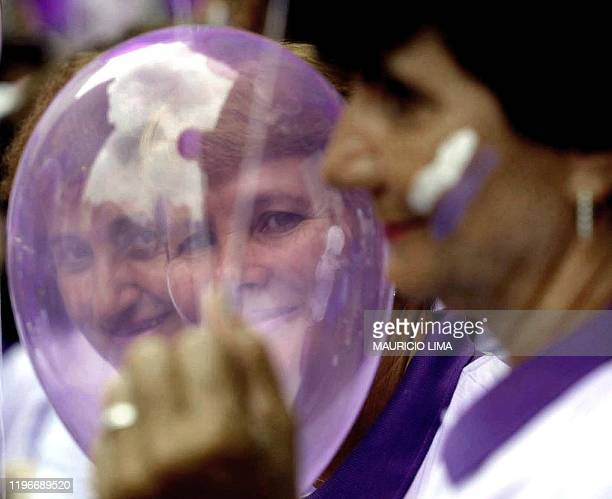 Two women look through a balloon 08 March 2001 during a ceremony for the International Women Day in Sao Paulo Brazil Dos mujeres observan el 08 de...