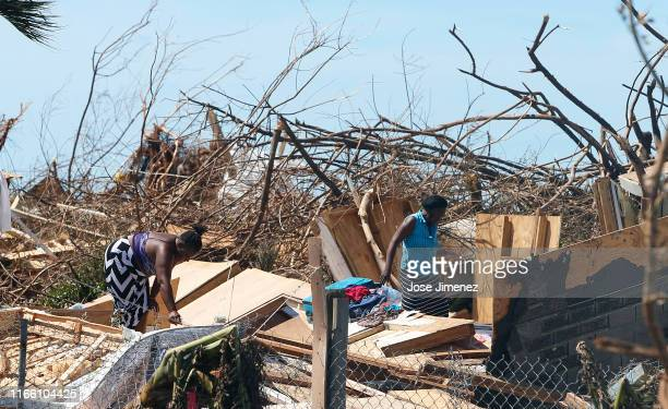 Two women look through the remains of a house in the Mud area on September 5, 2019 in Great Abaco Island, Bahamas. Hurricane Dorian hit the island...
