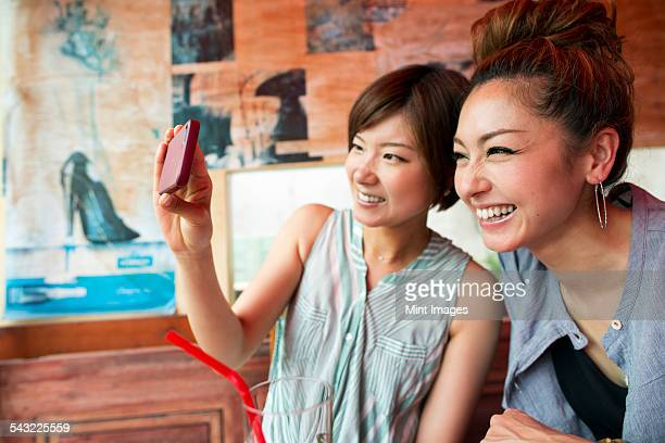 Two women looking at a cell phone, taking a selfie, sitting indoors.