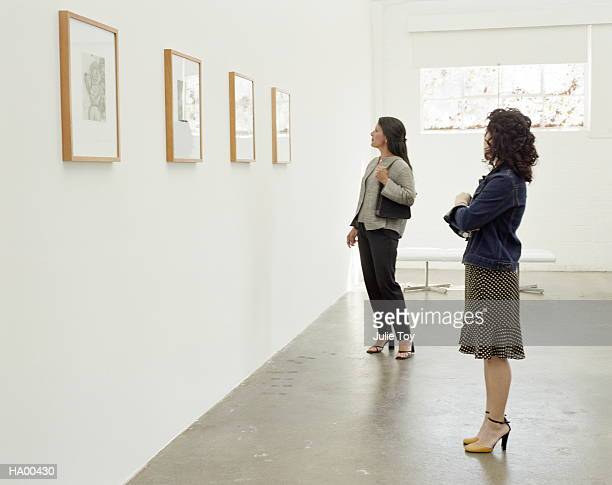 two women looking at exhibit  in art gallery - collection stock pictures, royalty-free photos & images