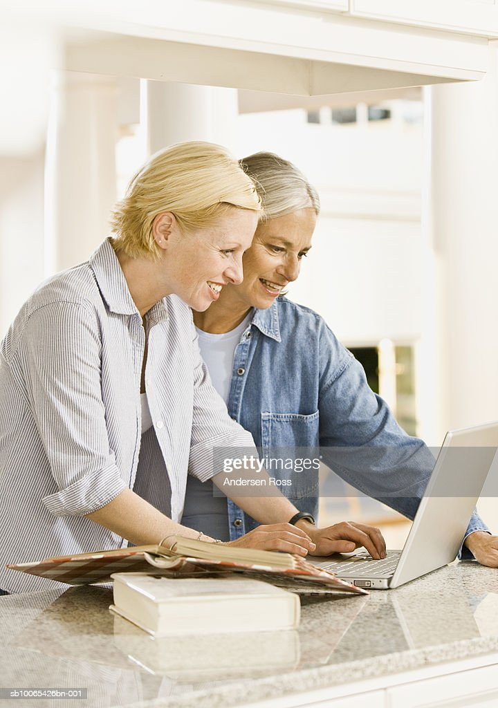 Two women looking at information on laptop : Foto stock