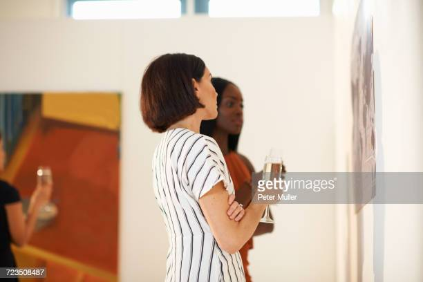 Two women looking at oil paintings at art gallery opening