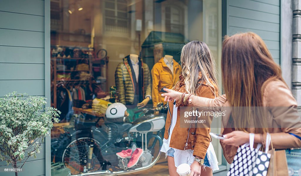 Two women looking at shop window of a boutique : Stock Photo