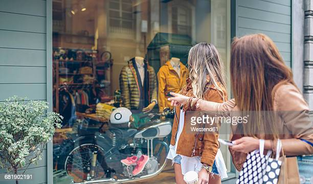 Two women looking at shop window of a boutique