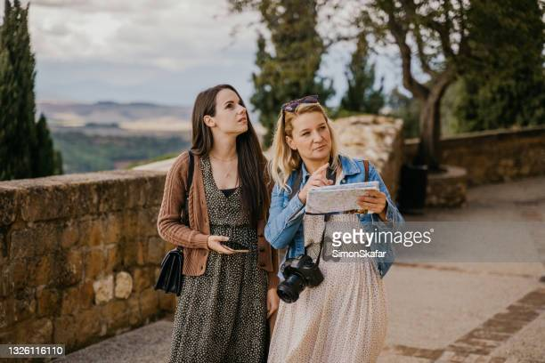 two women looking at the map - smurfs: the lost village stock pictures, royalty-free photos & images