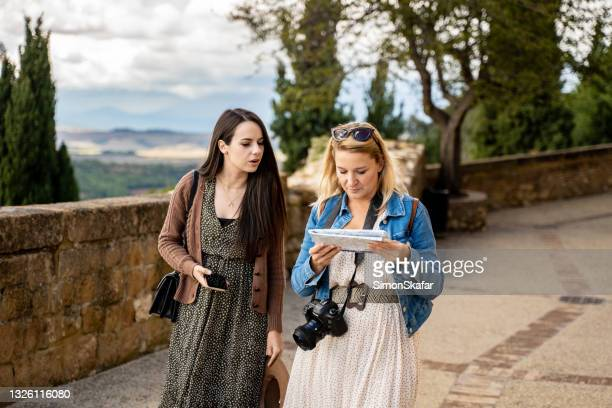 two women looking at the map while exploring the city - smurfs: the lost village stock pictures, royalty-free photos & images