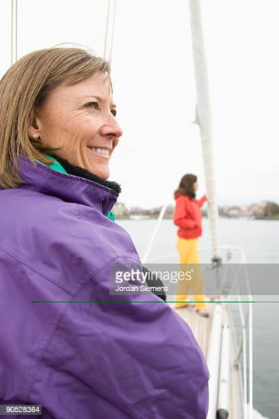 Two women looking out over the sea while on a sailboat.