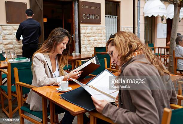 two women looking threw the menu at café - klaus vedfelt mallorca stock pictures, royalty-free photos & images