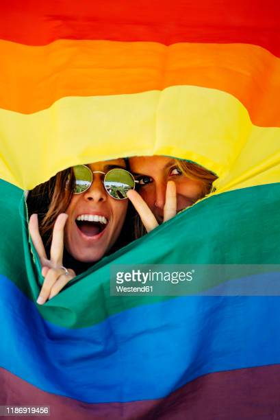 two women looking through a crack in a rainbow flag - slit clothing stock pictures, royalty-free photos & images