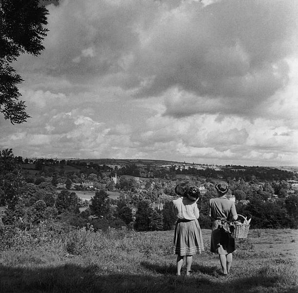 Two women looking towards an English village from a...