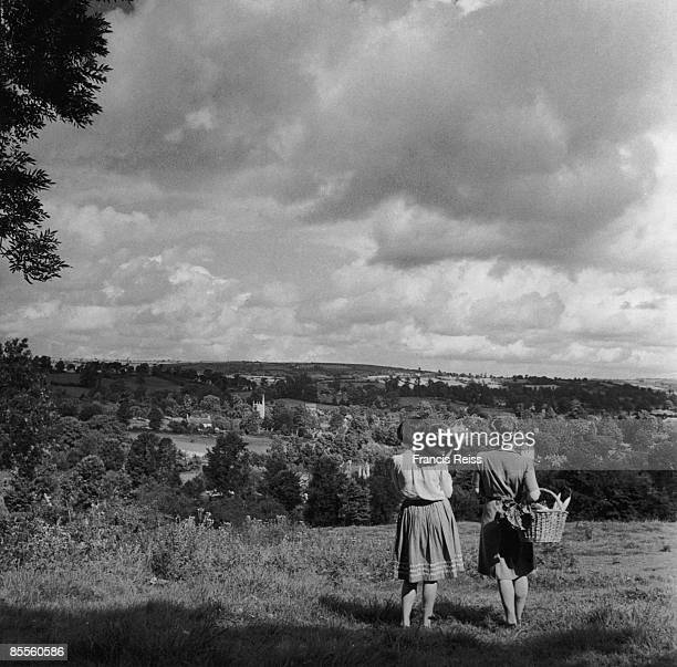 Two women looking towards an English village from a nearby hillside 1944 Original publication