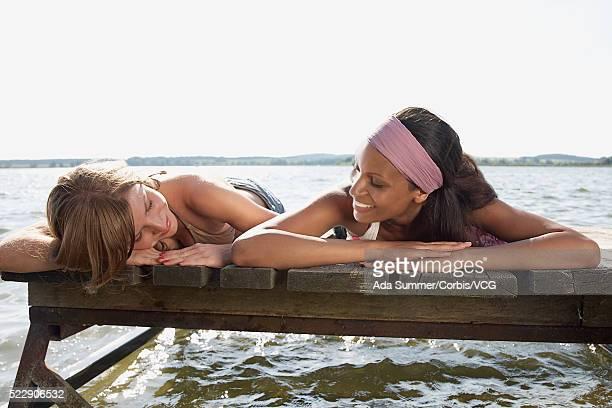 Two women lying on dock