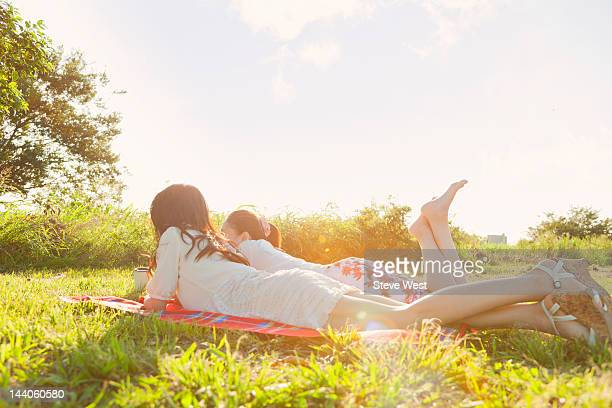 Two women lying on picnic blanket