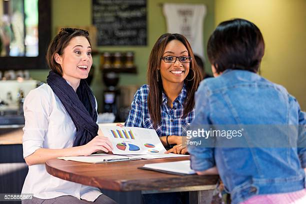 two women making a presentation to a potention client - pitcher stockfoto's en -beelden
