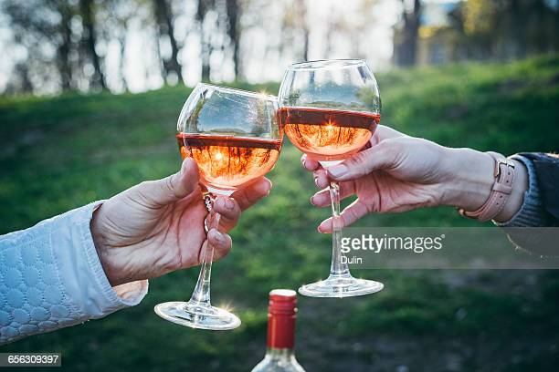 Two women making celebratory toast with glass of rose wine