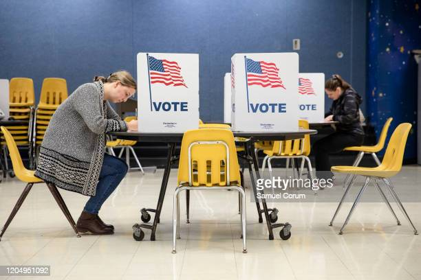 Two women mark down their votes on a ballots for the Democratic presidential primary election at a polling place in Armstrong Elementary School on...
