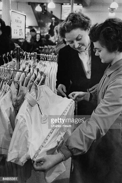 Two women measuring a silk blouse at a Marks Spencer store November 1955 Original Publication Picture Post 8437 Scientific Shopping unpub