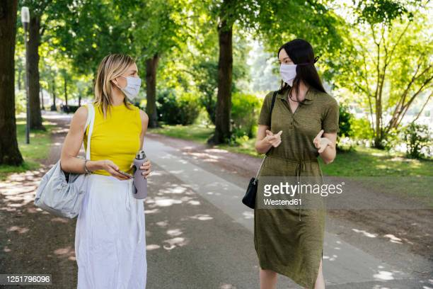 two women meeting in nature while wearing face masks - female friendship stock pictures, royalty-free photos & images