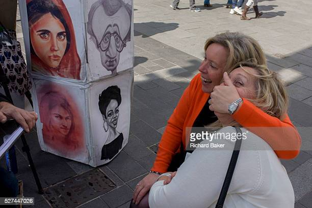 Two women mess about while having their portrait sketched by a street artist in Leicester Square One woman clamps her hand over her friend's mouth as...