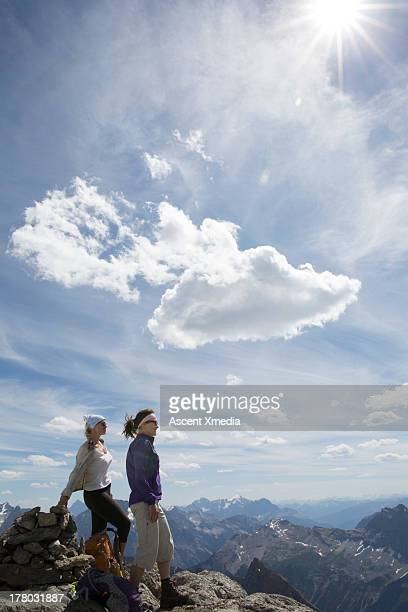 Two women mountaineers look off from mtn summit