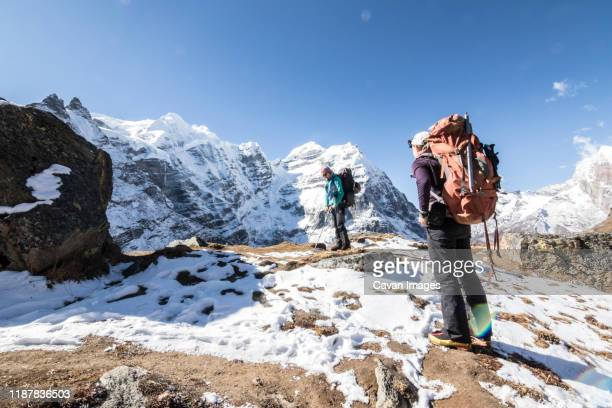 two women mountaineers take a break among a spectacular mountain scene - solu khumbu stock pictures, royalty-free photos & images