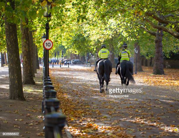 Two women mounted police officers riding down the Mall towards Buckingham Place.