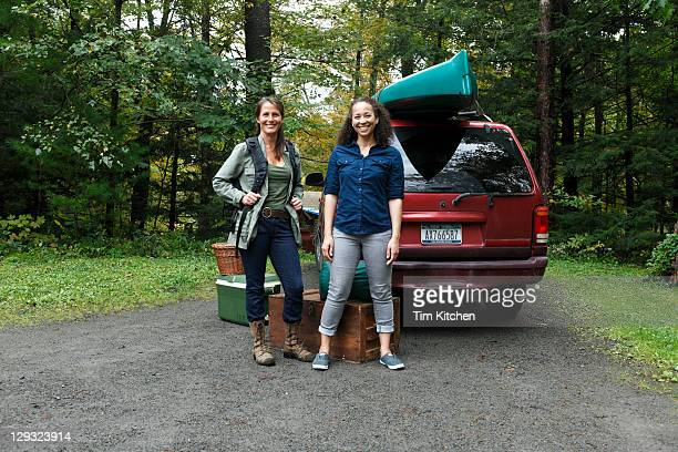Two women near SUV with camping gear