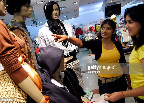 Two women observe outfits displayed on mannequins at a mall in Mumbai India on Thursday Nov 29 2007 India's economy grew last quarter at the slowest...
