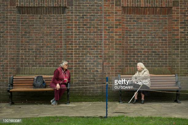Two women observe social distancing measures as they speak to each other from adjacent park benches amidst the novel coronavirus COVID-19 pandemic,...