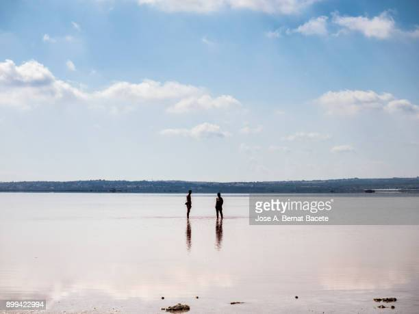 Two women of foot inside a lake speaking and sunbathing in the nature. Blue and sunny sky, in a lagoon of salty water in salt mines of Torrevieja, (Valencian Community), Spain.