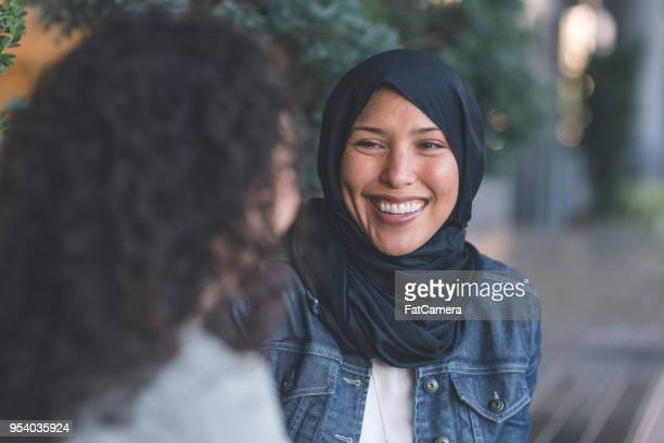 two women of middle eastern descent walk through the city - human rights stock pictures, royalty-free photos & images