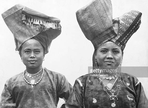 Two women of the Minangkabau people wearing traditional Minangnese headdresses and jewelry West Sumatra Indonesia circa 1930