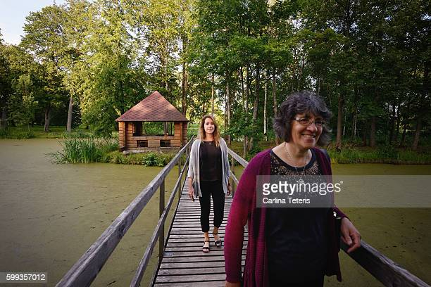 Two women on a bridge over a pond